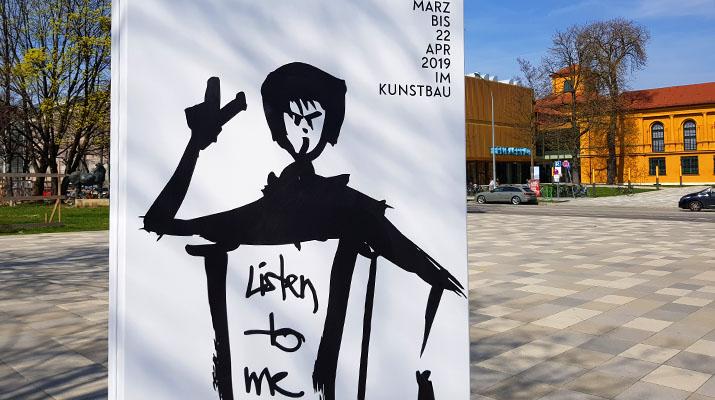 Plakat vor dem Kunstbau am Königsplatz zur Ausstellung Ein prekäres Singspiel von Beate Engl, Leonie Felle und Franka Kaßner