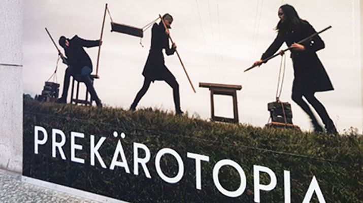 Plakat vor dem Eingang zur Aussstellung Prekärotopia im Kunstbau des Lenbachhauses in München