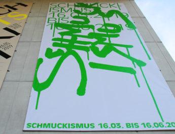 Plakat zur Ausstellung Schmuckismus in der Pinakothek der Moderne in München